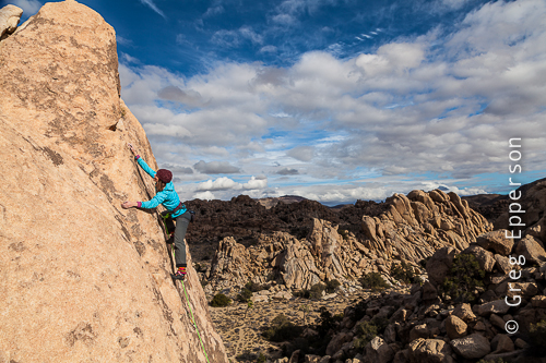 Elaina Arenz, co-owner Chicks Climbing and Skiing, applying just the right amount of pressure in the amazing and surreal, Joshua Tree, California.©Greg Epperson