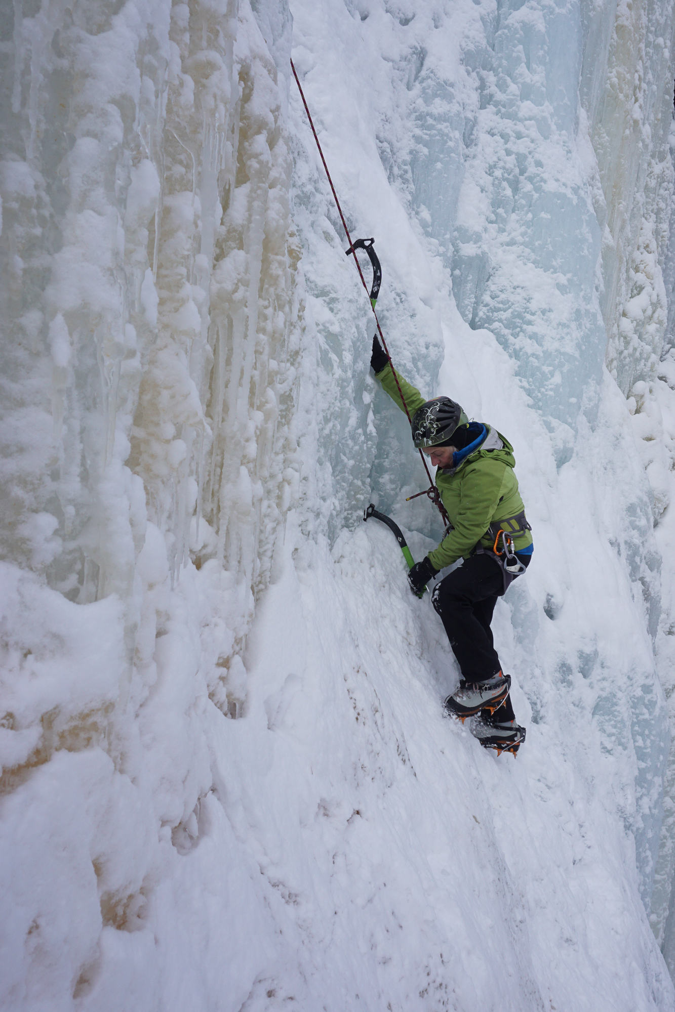 Chicks ice climbing clinic participant demonstrates how rock climbing relates to ice climbing by hanging on a straight arm